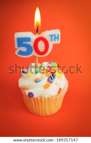Delicious cupcake with 50th candle on top on orange background - stock photo