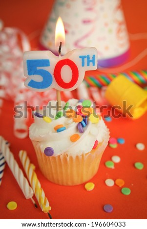Delicious cupcake with 50th candle on top with hat, candle and noisemaker in background - stock photo