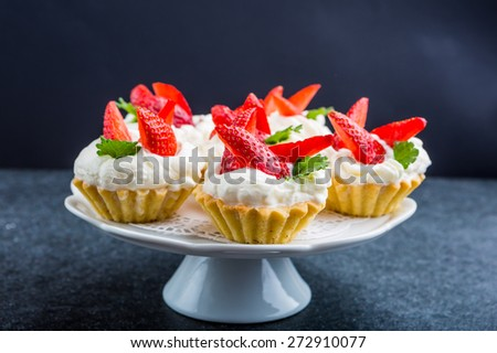 Delicious cupcake with whipped cream and fresh strawberries - stock photo