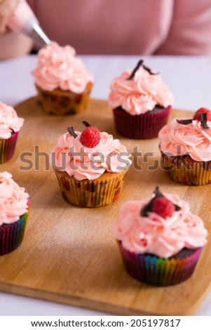 Delicious cupcakes decorated with whipped cream and fresh raspberries - stock photo