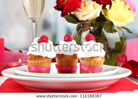 Delicious cupcakes with cream air on festive table close-up - stock photo