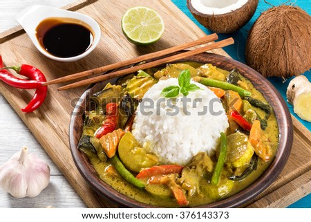delicious curry with vegetables, rice and prawns on a brown clay dish with chopsticks on a white old wooden table with soy sauce in a gravy boat, top view, close-up - stock photo