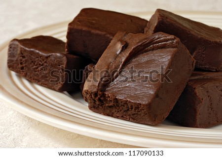 Delicious dark chocolate fudge on ceramic plate with elegant damask tablecloth as background.  Macro with shallow dof. - stock photo