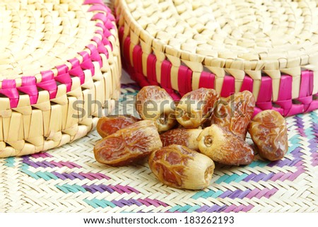 Delicious  dates on a mat made from date palm leaves. - stock photo