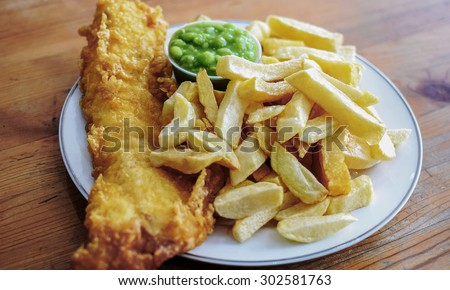 Delicious deep fried battered Cod Fish with Chips in a Fish and Chips restaurant in Greater London - stock photo