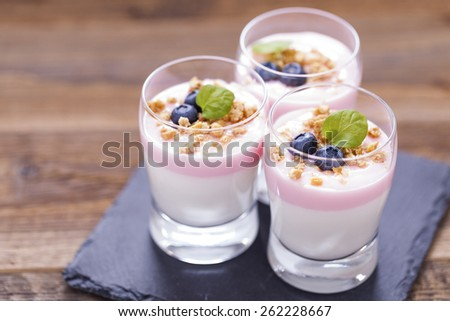 Delicious dessert, flakes flooded in two flavors yogurt with blueberries and fruit on a wooden board. dSLR photo - stock photo