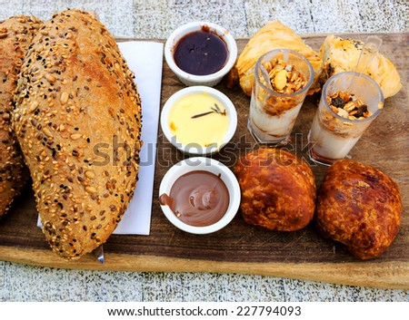 Delicious dessert (fresh bread with butter, strawberry jam and homemade chocolate spread, sweet and salty pastries and yogurt) at traditional Israeli breakfast at seaside cafe in Tel Aviv (Israel). - stock photo