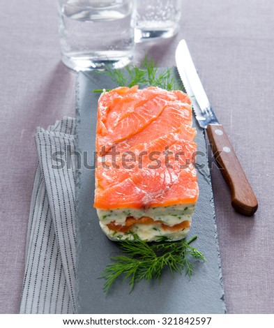 delicious dish with smoked salmon terrine with dill on gray granite gray board with a knife tablecloth close - stock photo