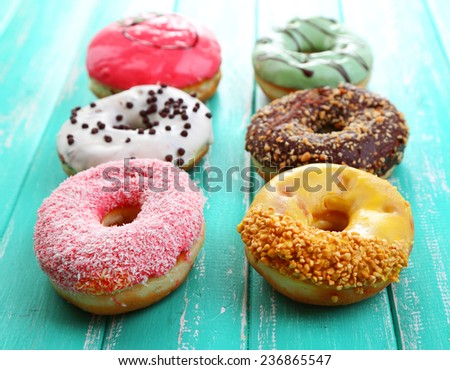 Delicious donuts with glaze on colorful wooden background - stock photo