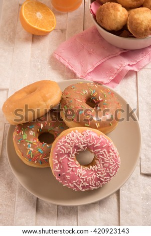 Delicious donuts with icing in a plate on marble background - stock photo