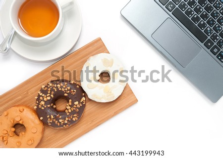 Delicious donuts with icing in wood plate and computer isolated on white - stock photo