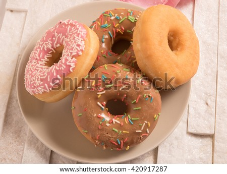 Delicious donuts with icing on plate on marble background - stock photo
