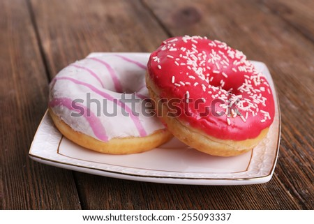 Delicious donuts with icing on plate on wooden background - stock photo