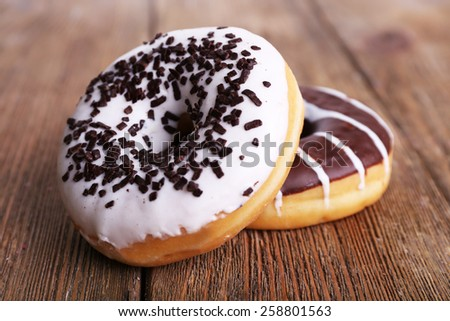 Delicious donuts with icing on wooden background - stock photo