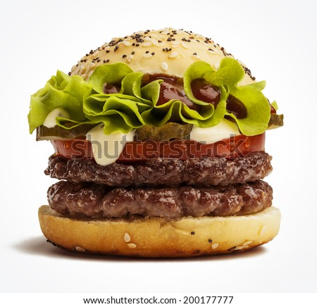 Delicious double burger with tomatoes, pickles and lettuce - stock photo