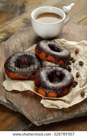 Delicious doughnuts with chocolate icing and cup of coffee on table close up - stock photo