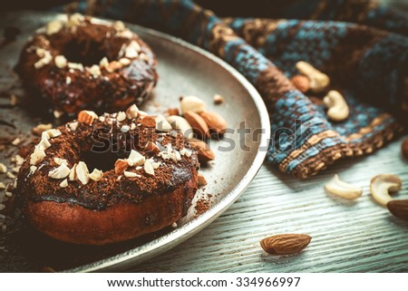 Delicious doughnuts with chocolate icing and nuts on table close up - stock photo