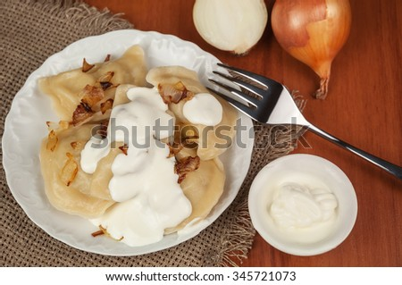 delicious dumplings (varenyky) with sour cream and fried onion - stock photo