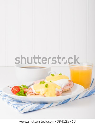 Delicious eggs benedict served with fresh coffee and juice. - stock photo
