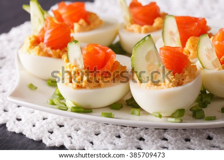 Delicious eggs stuffed with salmon, cheese and cucumber closeup on a plate. horizontal
