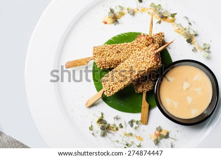 Delicious fish sticks with salmon and sauce on a plate with palm leaves and herbs - stock photo