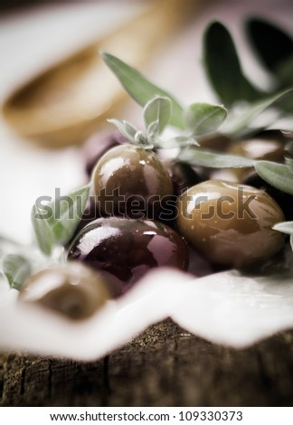 Delicious fresh black olives and leaves with shallow depth of field and copyspace - stock photo