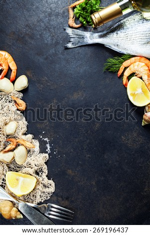 Delicious fresh fish and seafood on dark vintage background. Fish, clams and  shrimps with aromatic herbs, spices and vegetables - healthy food, diet or cooking concept - stock photo