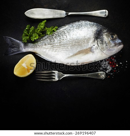 Delicious fresh fish on dark vintage background - stock photo