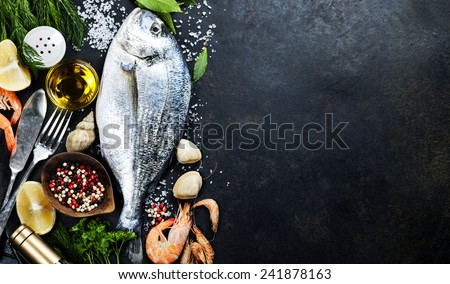 Delicious fresh fish on dark vintage background. Fish with aromatic herbs, spices and vegetables - healthy food, diet or cooking concept  - stock photo