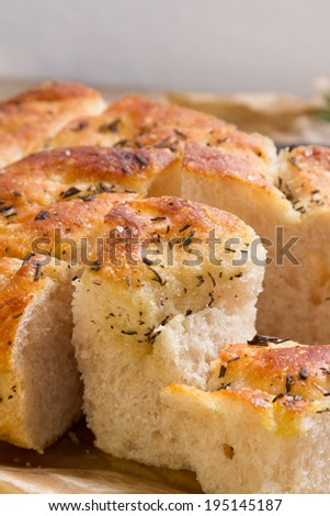 Delicious fresh focaccia bread with rosemary, pepper and rock salt. - stock photo