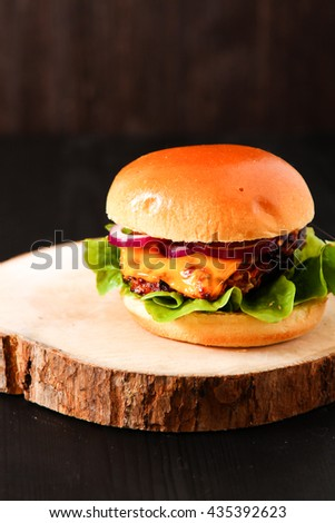 Delicious fresh homemade burger on dark serving board with spicy tomato sauce herbs over dark wooden background. Top view, copy space.  - stock photo