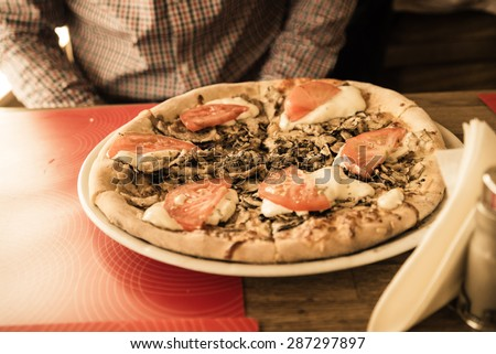 Delicious fresh pizza on table in restaurant - stock photo