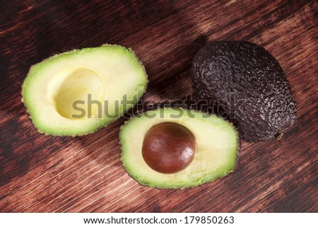 Delicious fresh ripe avocado cross section on brown wooden background, top view. Healthy fresh fruit eating. - stock photo