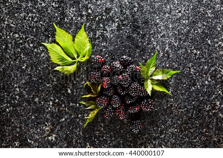 Delicious fresh ripe fruit of Blackberries and green leaves on a Marble table - stock photo