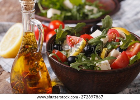 Delicious fresh salad with arugula, feta cheese and tomatoes close-up on a plate, horizontal  - stock photo