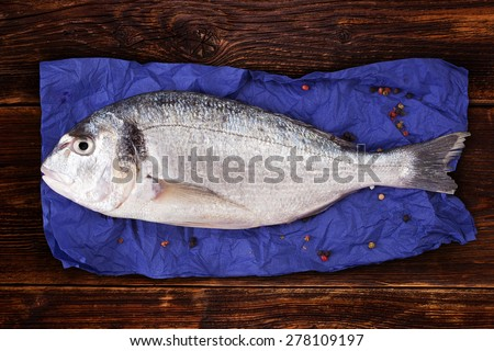 Delicious fresh sea bream fish on blue napkin with colorful peppercorns on brown vintage wooden background. Culinary healthy cooking. - stock photo