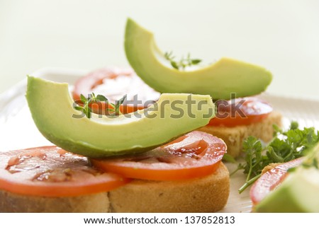 Delicious fresh slice of avocado with tomato and thyme on sliced toasts. - stock photo