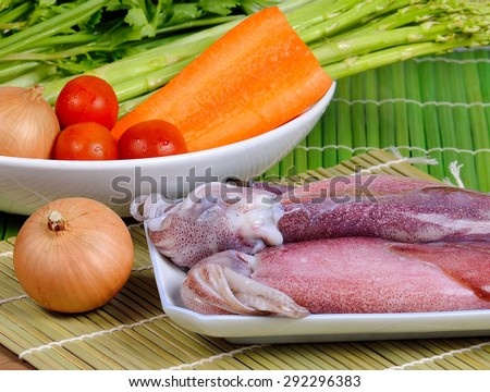 Delicious fresh squid and vegetables on wooden background - stock photo