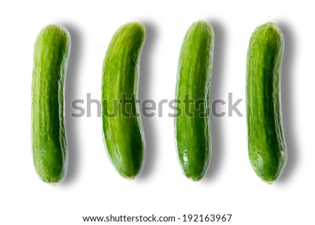 Delicious fresh whole green mini cucumbers ready to be consumed arranged in a row with lateral shadows on a white background - stock photo