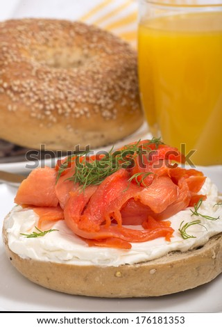 Delicious freshly baked Everything Bagel with cream cheese, lox (also known as salmon) and dill served with fresh orange juice - stock photo
