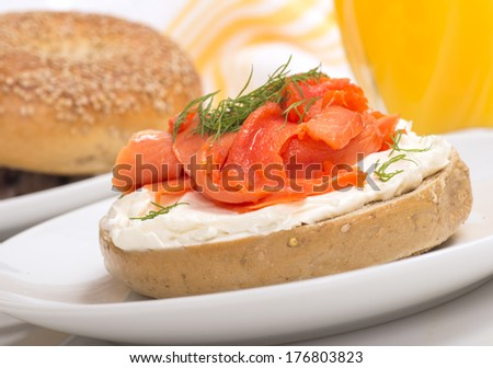 Delicious freshly baked Everything Bagel with cream cheese, lox and dill served with fresh orange juice - stock photo