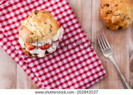 Delicious freshly baked scones with thick cream, jam and strawberries on a red and white checkered background - stock photo