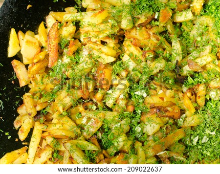 Delicious freshly cut potato chips and chopped herbs cooking in oil on a BBQ on a summer picnic, close up overhead view - stock photo