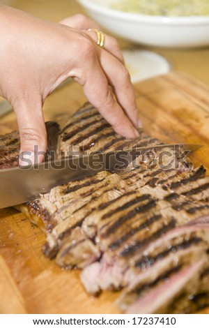 Delicious freshly prepared seared sirloin on a wooden cutting board, in the process of being cut by the chef. - stock photo
