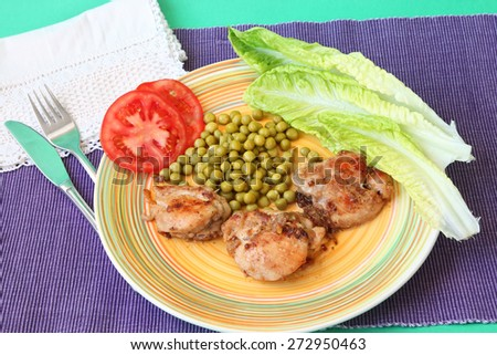 Delicious fried and stew chicken fillet with green peas, sliced fresh tomato and lettuce leaf. Served on a bright color's plate and napkin. Homemade cooking - stock photo