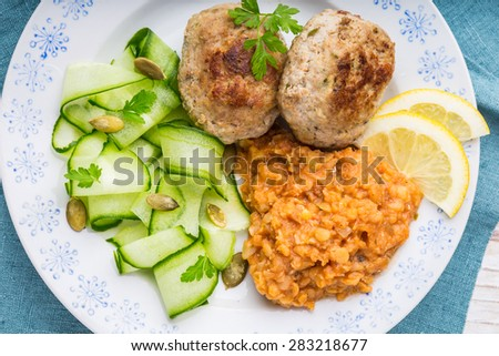 Delicious fried beef meatball, cooked lentils and salad with fresh cucumber on a white plate - stock photo
