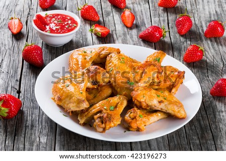 delicious fried chicken wings on a white dish with strawberry sauce on a gravy boat and strawberries on a wooden table, close-up - stock photo