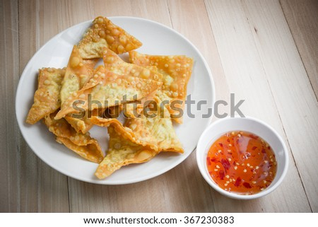 Delicious Fried dumpling crispy with spicy sauce on the wood table - stock photo
