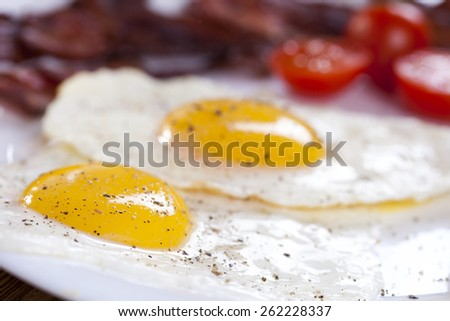 Delicious fried egg with spices, bacon, croutons and tomatoes on a white plate. Composition on a wooden table in the background spices and entrees. Photo made by dSLR camera - stock photo