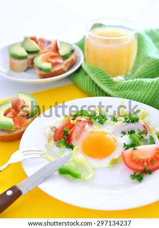 Delicious fried egg with tomato slices, capsicum, leek and parsley served with juice and salmon avocado sandwiches. Can be served for breakfast or lunch. Copy space - stock photo
